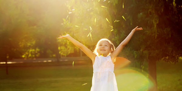 child throwing grass into the air